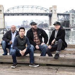 Chefs Angus An, Robert Belcham, Hamid Salimian and Joël Watanabe sitting on a pier at Granville Island